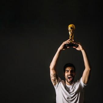 Uomo con il trofeo fifa che celebra la vittoria