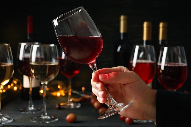 Uomo con in mano un bicchiere di vino contro uno sfondo scuro