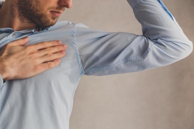 Uomo con iperidrosi che suda molto male sotto l'ascella in camicia blu, su grigio.