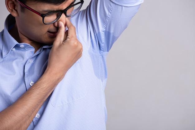 Uomo con iperidrosi sudorazione sui suoi vestiti. concetto di assistenza sanitaria.