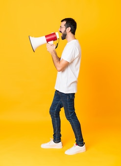 Uomo con la barba che grida attraverso un megafono