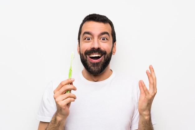 Uomo con la barba che pulisce i denti sopra fondo bianco isolato
