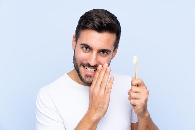 Uomo con la barba che pulisce i suoi denti sopra la parete isolata