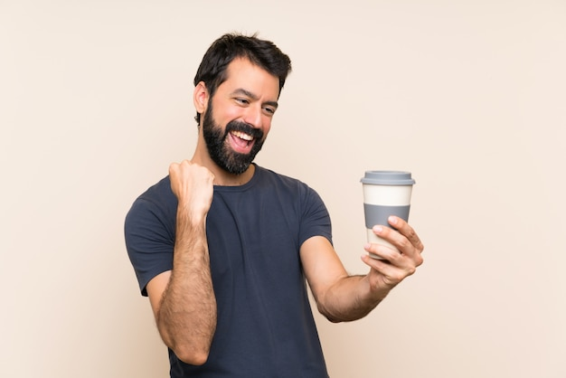 Uomo con la barba che tiene un caffè che celebra una vittoria
