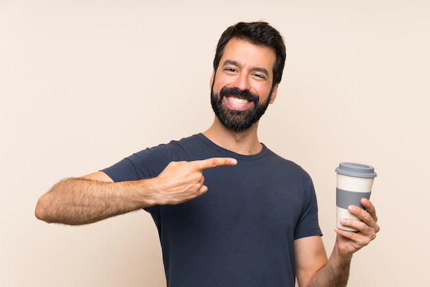 Uomo con la barba che tiene un caffè e che lo indica