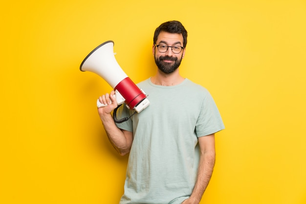 Uomo con la barba e camicia verde in possesso di un megafono