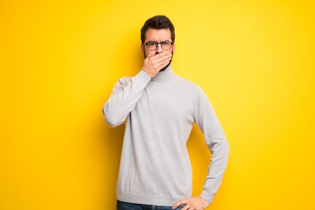 Uomo con la barba e il collo alto che copre la bocca con le mani per dire qualcosa di inappropriato