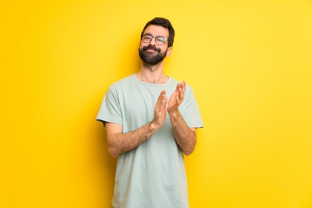 Uomo con la barba e la camicia verde che applaudono dopo la presentazione in una conferenza