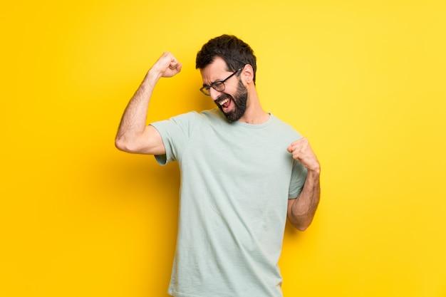 Uomo con la barba e la camicia verde che celebra una vittoria