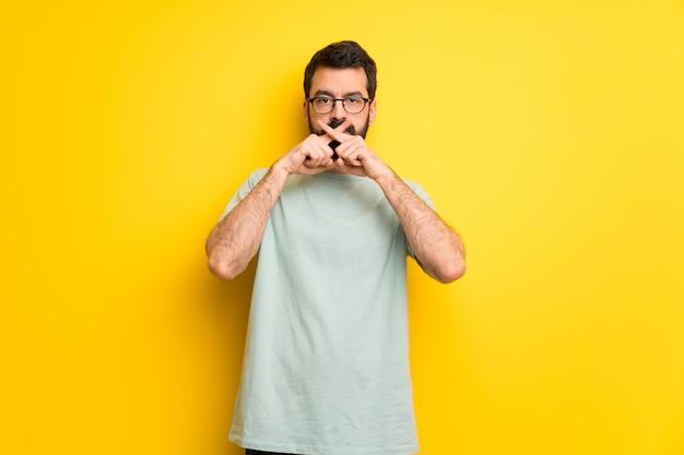 Uomo con la barba e la camicia verde che mostra un segno di gesto di silenzio