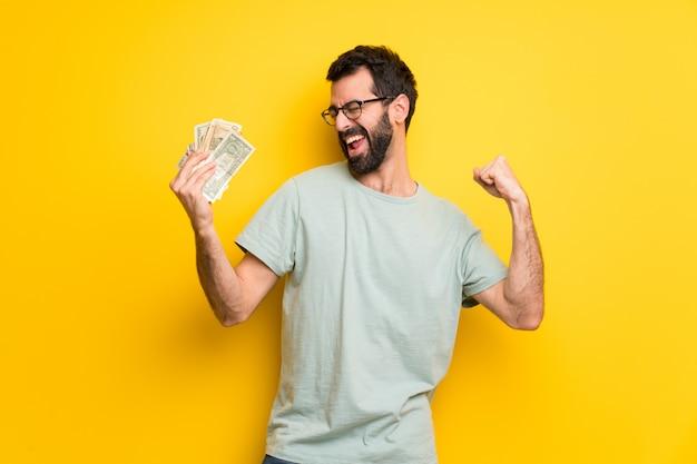 Uomo con la barba e la camicia verde che prendono molti soldi