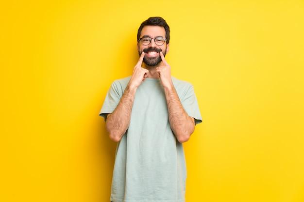 Uomo con la barba e la camicia verde che sorride con un'espressione felice e piacevole