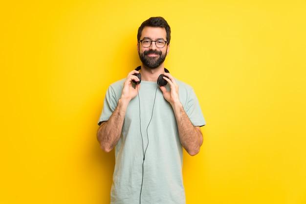 Uomo con la barba e la camicia verde con le cuffie