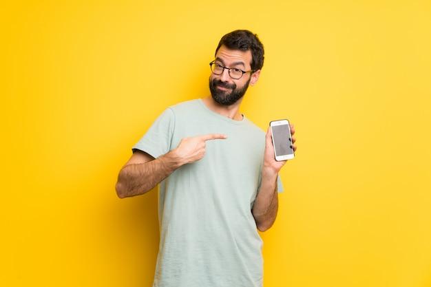 Uomo con la barba e la camicia verde felice e indicando il cellulare