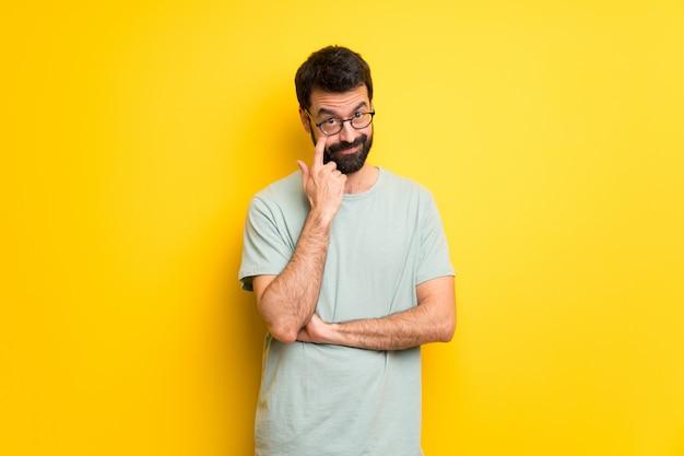 Uomo con la barba e maglietta verde che guarda in avanti