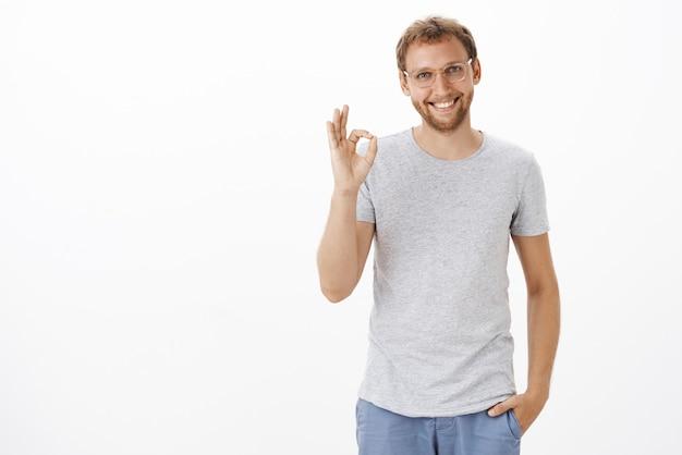 Uomo con la barba lunga intelligente e disponibile amichevole in occhiali trasparenti e abbigliamento casual che tiene la mano in tasca sorridendo casualmente assicurato e mostrando il gesto ok o ok sul muro bianco