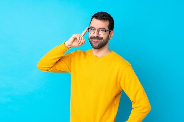 Uomo con la barba sopra la parete blu isolata