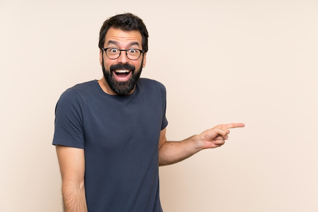 Uomo con la barba sorpreso e puntando il dito verso il lato