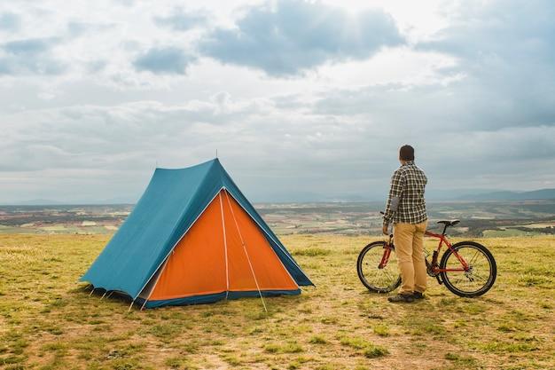 Uomo con la bici in piedi accanto alla tenda