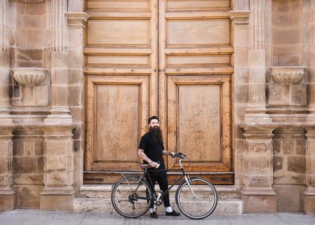 Uomo con la bicicletta che sta davanti alla grande parete di legno d'annata chiusa