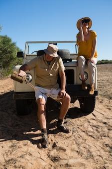 Uomo con la bottiglia della tenuta della donna mentre sedendosi sul veicolo
