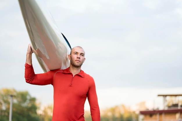 Uomo con la canoa sulla spalla che osserva via