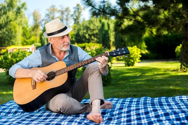 Uomo con la chitarra che si siede su una coperta da picnic