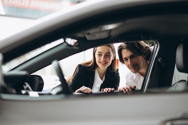 Uomo con la donna che sceglie un'automobile in una sala d'esposizione dell'automobile