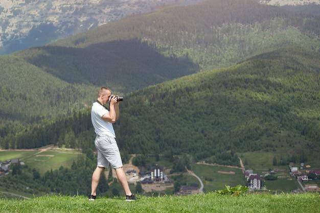 Uomo con la macchina fotografica che sta su una collina e su una natura di fotografia. giorno d'estate