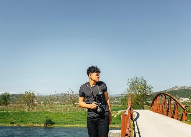 Uomo con la macchina fotografica digitale che osserva via