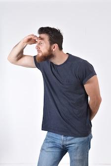 Uomo con la mano nella parte anteriore che osserva via sul bianco
