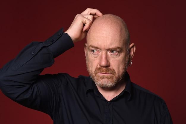 Uomo con la mano sulla testa su sfondo rosso