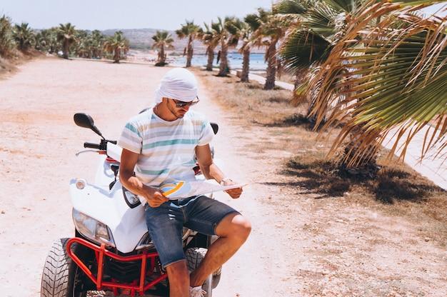Uomo con la mappa che viaggia su atv in riva al mare