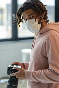 Uomo con la maschera che tiene la fotocamera