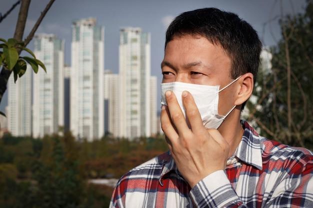 Uomo con la maschera nella città, concetto di inquinamento atmosferico