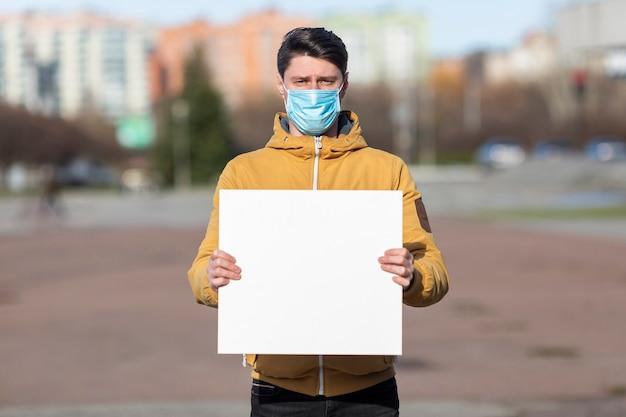 Uomo con la mascherina chirurgica con cartello bianco