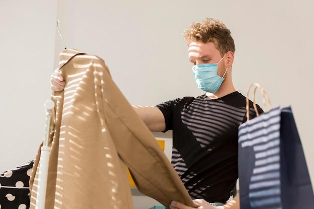 Uomo con la mascherina medica che esamina i vestiti