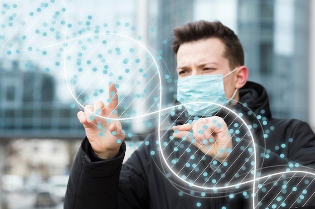 Uomo con la mascherina medica che esamina la struttura del dna