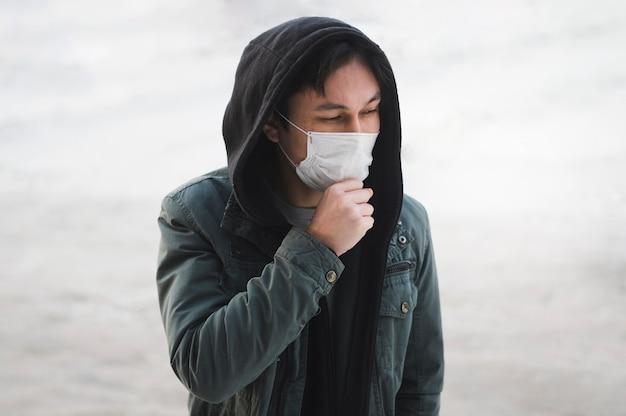 Uomo con la mascherina medica che propone all'esterno