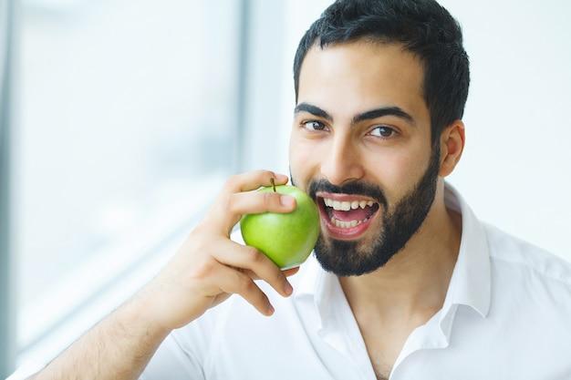 Uomo con la mela. bello maschio con il sorriso bianco, denti sani.