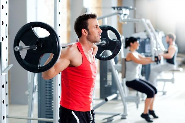 Uomo con la palestra di attrezzature di allenamento con pesi manubri
