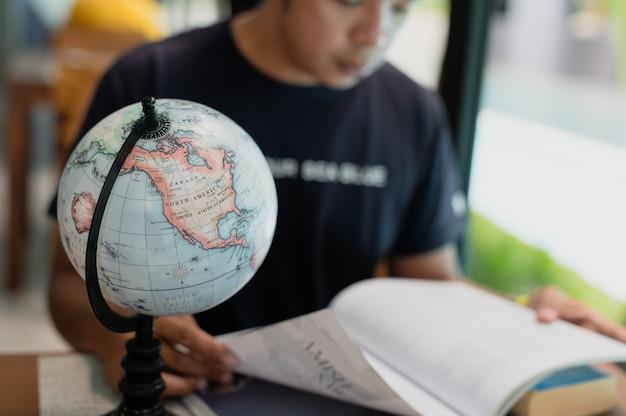 Uomo con la pianificazione del libro vacanza in messa a fuoco selettiva, prenotazione di biglietti, viaggi e vacanze concetto