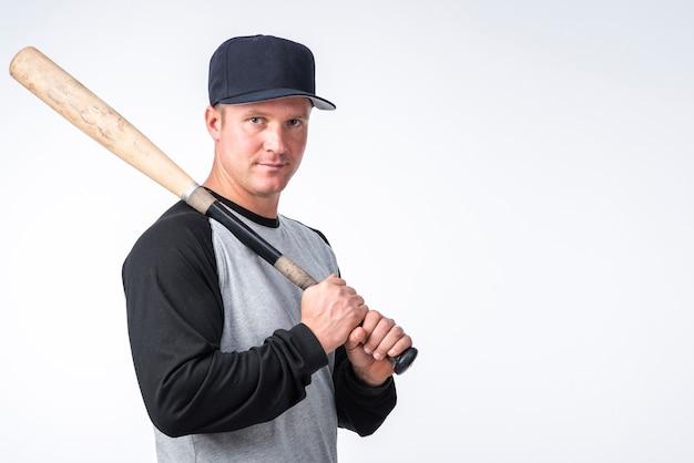 Uomo con la protezione che propone con la mazza da baseball