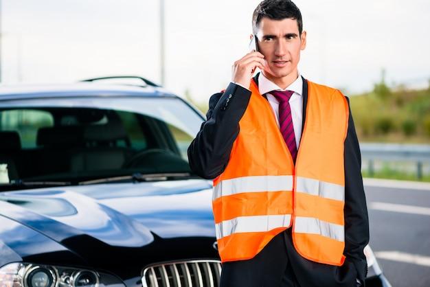 Uomo con la ripartizione dell'automobile che chiama la società di rimorchio