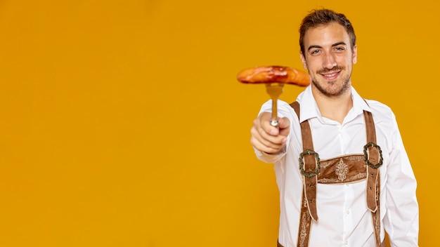 Uomo con la salsiccia tedesca e lo spazio della copia