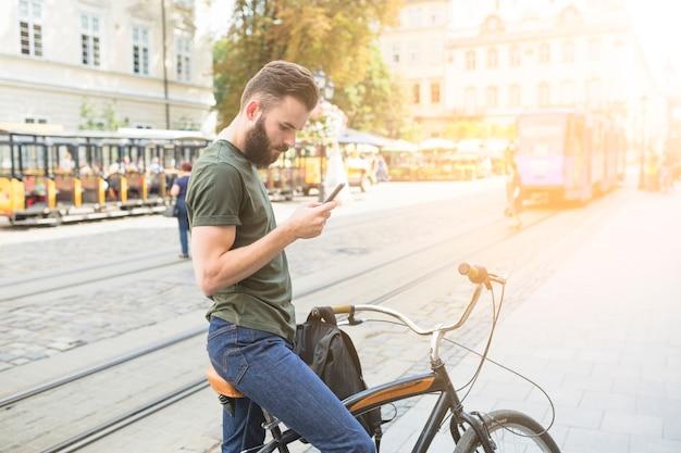 Uomo con la sua bicicletta tramite smartphone