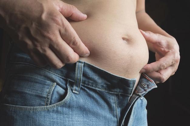 Uomo con la sua pancia isolato su sfondo nero. concetto di sovrappeso e perdita di peso.