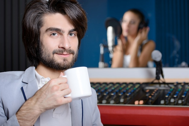 Uomo con la tazza di caffè in studio di registrazione, ragazza vaga che canta