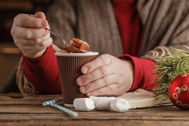 Uomo con la tazza di cioccolata calda con marshmallow, bevanda invernale di natale
