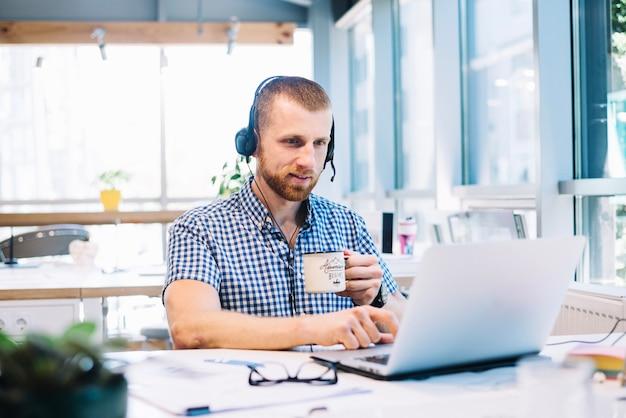 Uomo con la tazza e headsetworking sul computer portatile